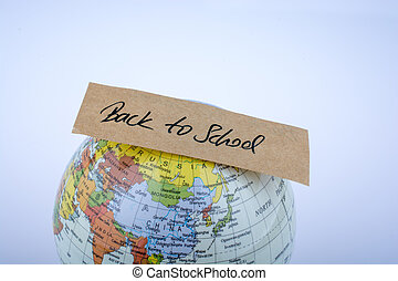 Globe and back to school title on a white background