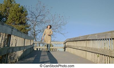 Woman starts running on the bridge to the lake. Red leaf.