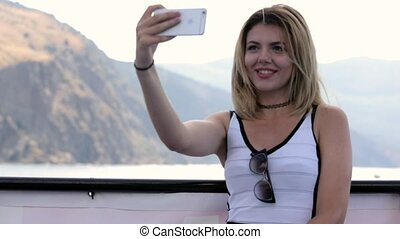 Cute blonde doing selfie in the bay in the mountains - Cute...