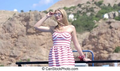 Sexy blonde with long hair in dress and sunglasses traveling...