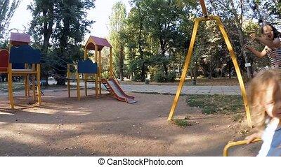 SLOW MOTION. Children ride on the swings - SLOW MOTION. Cute...