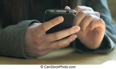 Schoolgirl sitting at a desk holds a smartphone - The...