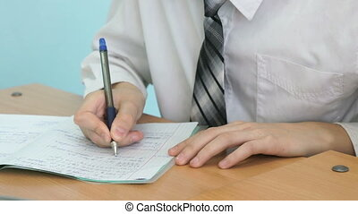 The learner writing the text in the copybook during the...