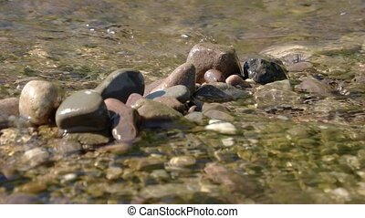 pile of gray river rocks over an out of focus river background