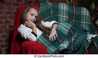 Girl watching gaze lying in a chair wrapped in a blanket -...