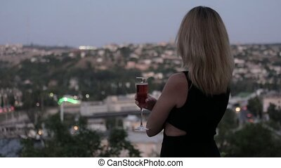Seductive blonde in a black evening dress drinking champagne...