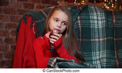 Girl in a red sweater thoughtfully sits with a cup of tea