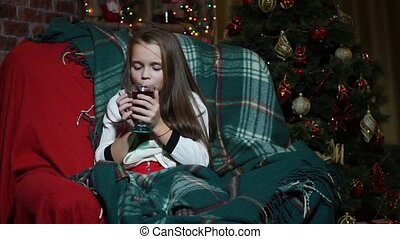 Closeup girl drinking tea wrapped in a blanket near a Christmas tree