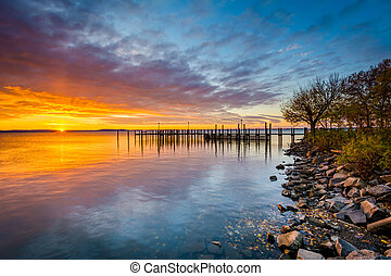 Sunrise over dock and the Chesapeake Bay, in Havre de Grace,...