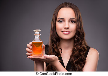 Young woman with bottle of perfume