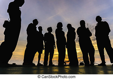 Friends - Low angle view silhouette of offshore workers...