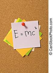 E=MC2 formula write on the paper attached on the cork board