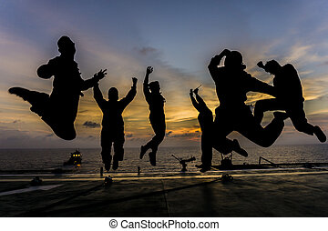 Friends - Silhouette of offshore workers jumping on helipad...