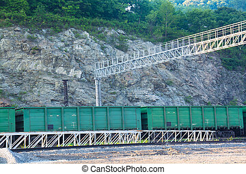 Freight cars on a rail near steep slope. Summer day
