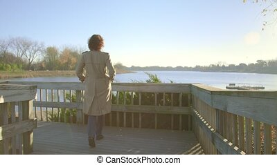 Woman goes on the bridge to the lake.