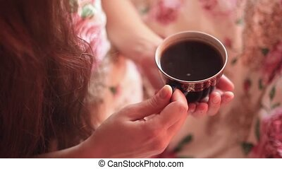 girl drinking coffee in bed - Girl sits in a white coat in...