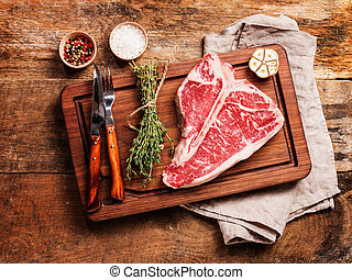 Raw T-bone Steak for grill or BBQ on cutting board over aged...