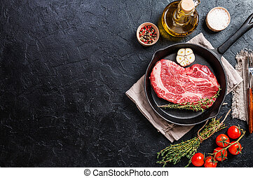 Raw fresh ribeye steak on grill pan on black stone...