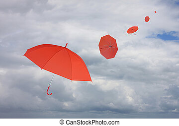 Red umbrella blown by wind.