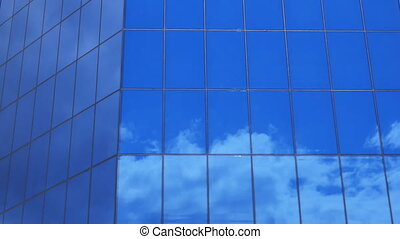 clouds reflection on a glass facade - modern office Building - time lapse