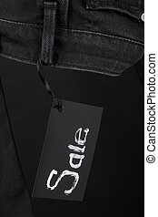 Sale sign hanging on  black  jeans with  background. Friday . Close up.