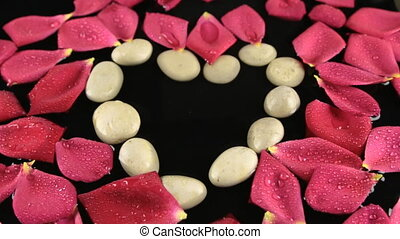 Wind blowing on heart made of stones and rose petals floating in the water.