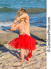 Christmas baby girl playing on the beach near the sea