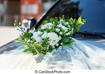 wedding car decorated with flowers on the hood.