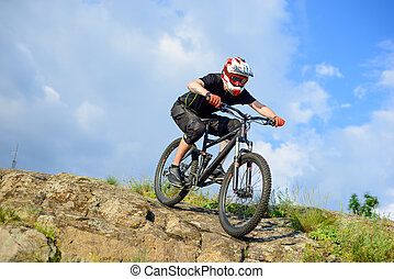 Professional Cyclist Riding the Bike Down Rocky Hill. Extreme Sport.