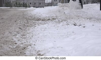Man cleans snow from street sidewalk via snow removal...