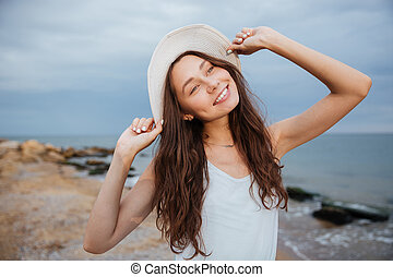 Smiling cute young woman in hat on the beach