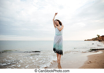 Smiling beautiful young woman dancing on the beach - Smiling...