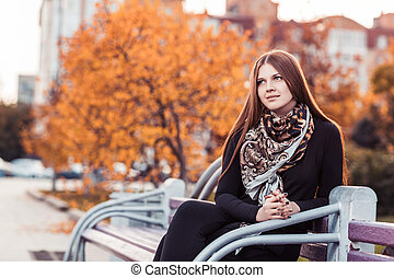 Young woman sitting at the bench - Young beautiful woman...