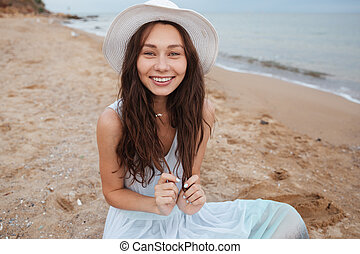 Smiling woman in white dress and hat sitting on beach -...