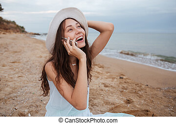 Happy woman talking on mobile phone and laughing at beach -...