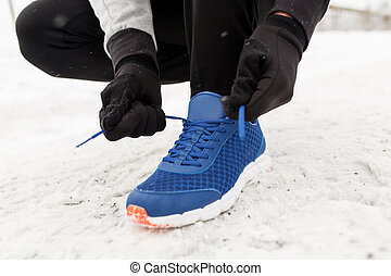 close up of man tying shoe lace in winter outdoors -...