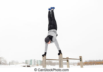 young man exercising on parallel bars in winter - fitness,...