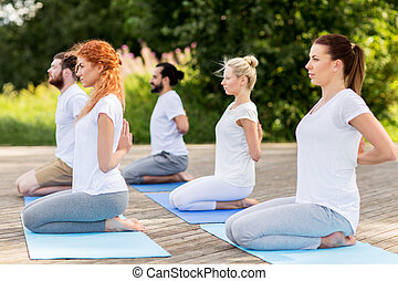 people making yoga in hero pose outdoors - yoga, fitness,...