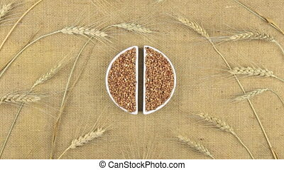 Zoom dish with buckwheat grains and spikelets of wheat lying on sackcloth.