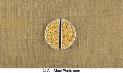 Zoom dish with pea grains and spikelets of wheat lying on...