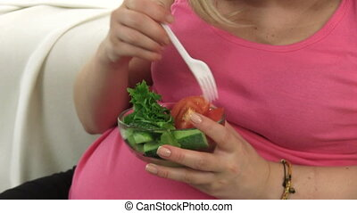 Pregnant Woman Eating Vegetable - Pregnant woman eating a...