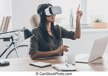 Using VR technologies. Confident young woman in virtual...
