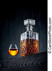 Glass and carafe of whiskey on a black wooden table