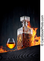 Burning carafe and glass of whiskey  on a black wooden table