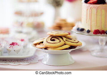 Spiral cookies, cake and cupcakes laid on table. - Cookies...