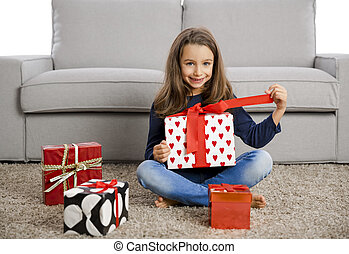 Little girl opening presents - Happy little girl at home...