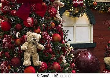 Christmas decoration, tree festooned with balls, lights, gifts and bears. House decorated in the background.