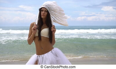 Woman in white indian feather hat at the beach - Sensual...
