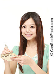 young Japanese woman writing in notebook - studio shot of...