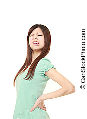 Japanese woman suffers from lumbago - studio shot of young...